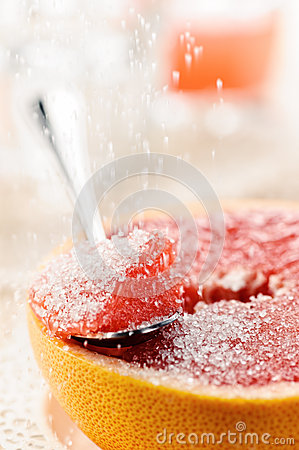 Piece of red grapefruit with sugar, fruit dessert