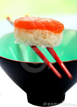 A piece of salmon sashimi balanced on a pair of chopstick