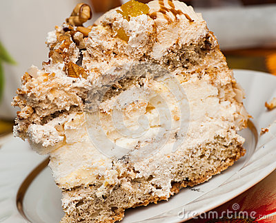 Piece of sweet cake with a walnut, cream and fruit