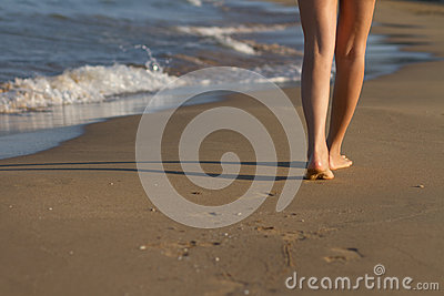 Piedi della ragazza che svegliano sulla sabbia