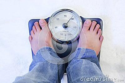 Piedi sulla scala del peso