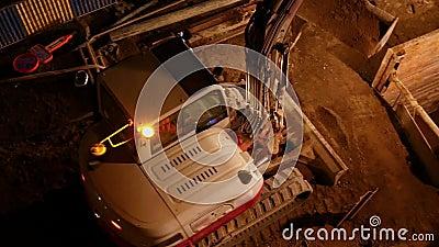Piedra de oruga que trabaja en la construcción por la noche metrajes