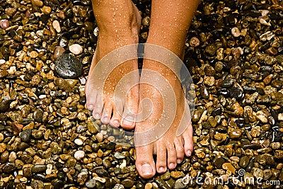Pieds bronzés sur des pierres