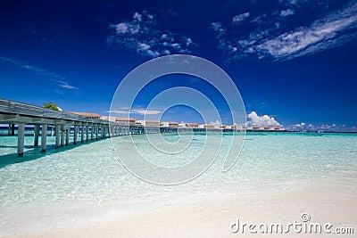 Pier with aqua villas on the horizon