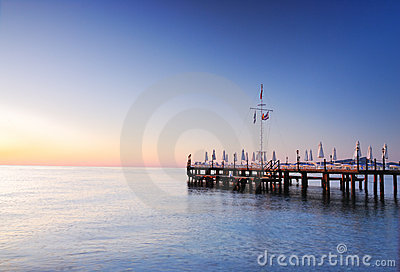 Pier lighted by sunrise glowing