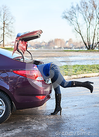 Piernas femeninas del tronco de coche