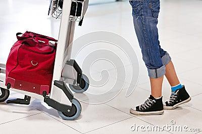 Piernas y pies de la mujer con el coche del equipaje