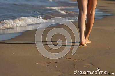 Pies de la muchacha que despiertan en la arena