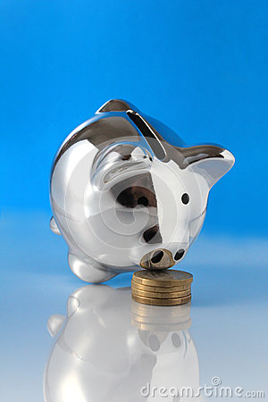 Pig bank sniffing coins on blue background
