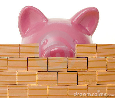 Piggy bank behind a bricks wall