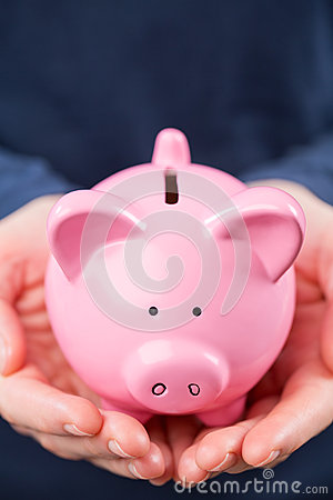 Piggy Bank in the Hands of a Woman