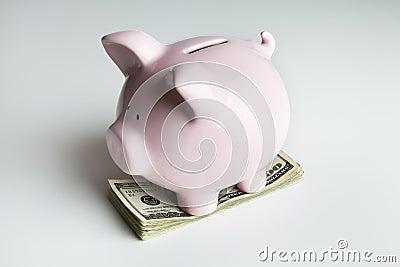 Piggy bank on a stack of 100 dollar bills