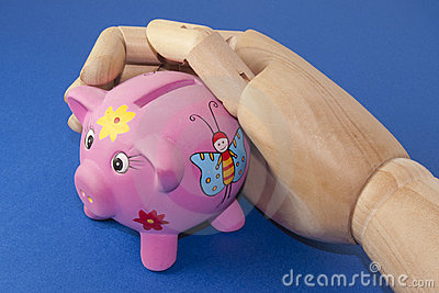 Piggy bank in a wooden hand