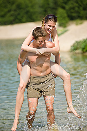 Piggyback - happy couple enjoy sun at lake