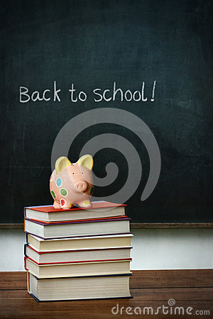 Piggybank and books in front of chalkboard