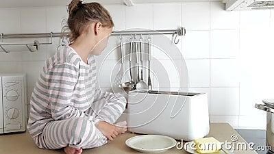 Pigiami d'uso della ragazza che mettono pane nel tostapane stock footage