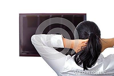 Piękna brunetka jest odpoczywa przy TV