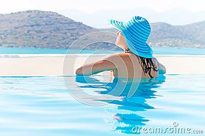 Piękna brunetka relaksuje w pływackim basenie