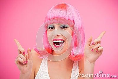 Piękna kobieta jest ubranym różową perukę