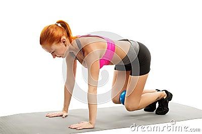 Piękna zmysłowa kobieta robi sprawności fizycznej z piłką