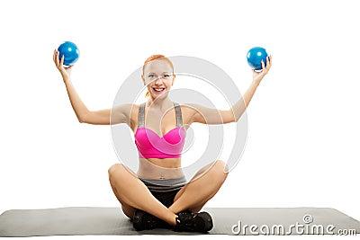 Piękna zmysłowa kobieta robi sprawności fizycznej z piłkami
