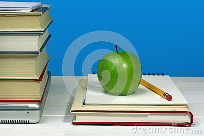Pile of books, laptop, green apple and pencil