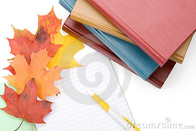 Pile of books, writing-book, pen and autumn leaves