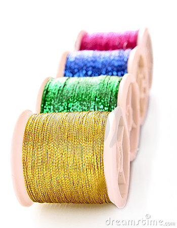 Pile of coloured bobbins of lurex thread isolated