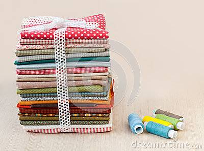Pile of folded textile with spool of thread