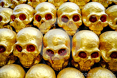 Pile of golden skulls with red eyes. closeup