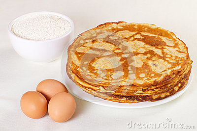 Pile of pancakes with some flour and eggs