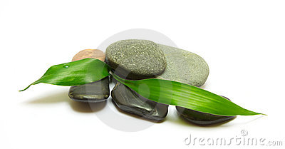Pile of stones and bamboo leafs on white