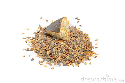 Pile of Tan Sesame Seeds with Piece of Cookie