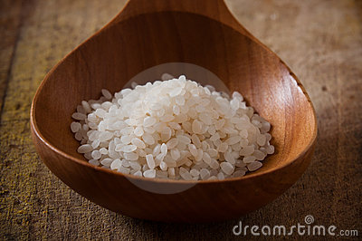 Pile of white rice in a wooden spoon