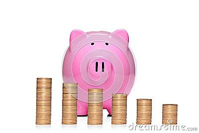 Pilha de moedas na frente do banco piggy cor-de-rosa