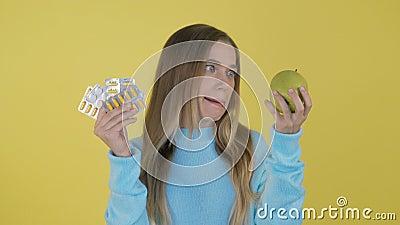 Pillen beter! De pillen van de vrouwenholding verschroeien pakvitamine c in één hand en appel in een andere Keus tussen natuurlij stock video