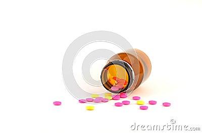 Pillole che si rovesciano dalla bottiglia isolata su bianco