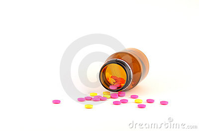 Pills spilling out of bottle isolated on white