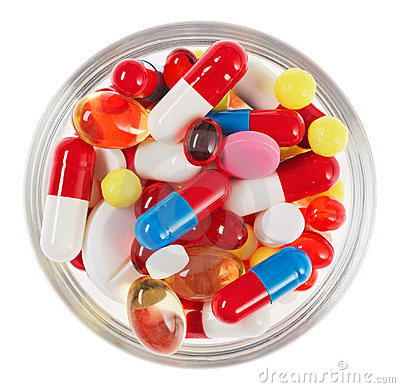 Pills, tablets and drugs heap in glass