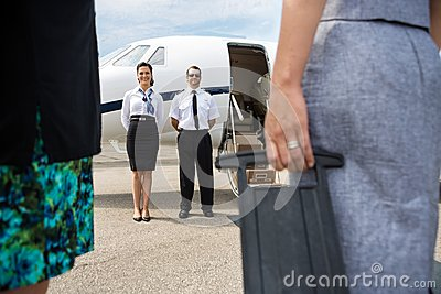 Pilot And Airhostess Standing Near Private Jet
