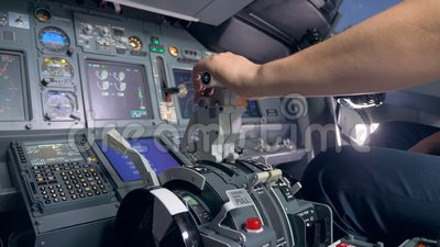 A pilot pulls a lever in a plane  Man uses a lever to pilot a plane