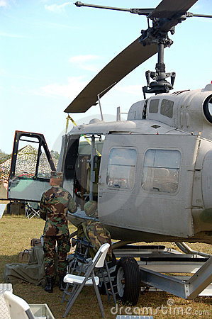 Pilot standing next to ground attack helicopter