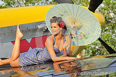 Pin up girl posing with a vintage fighter plane