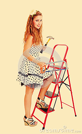 Pin up woman on ladder with a hammer, toned