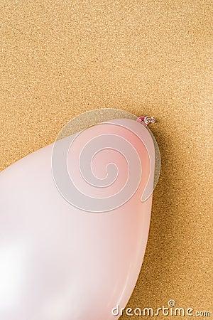 Pink balloon on cork noticeboard in office