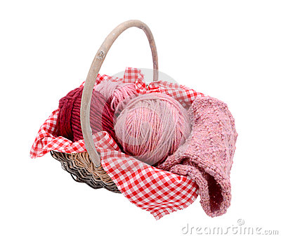 Pink balls of yarn with knitting in a basket