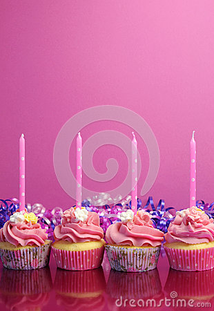Pink birthday cupcakes with polka dot candles - Vertical with copy space.