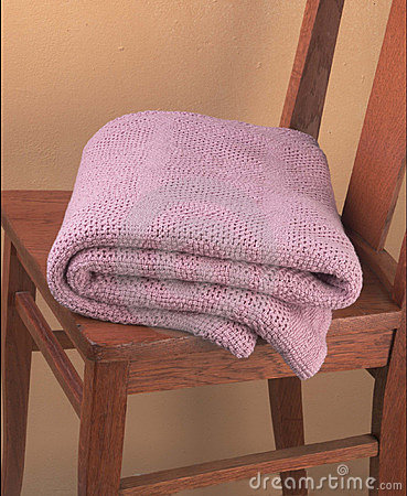 Pink blanket folded on wooden chair