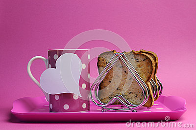 Pink breakfast tray with polka dot coffee tea cup mug and heart shape toast rack with wholemeal toast for Mothers Day, birthday or