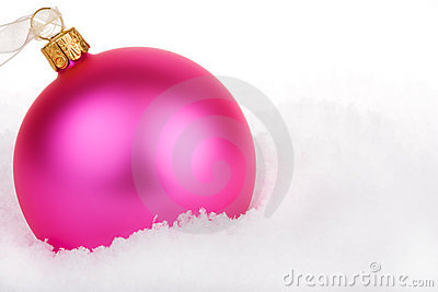 Pink Christmas bauble on snow